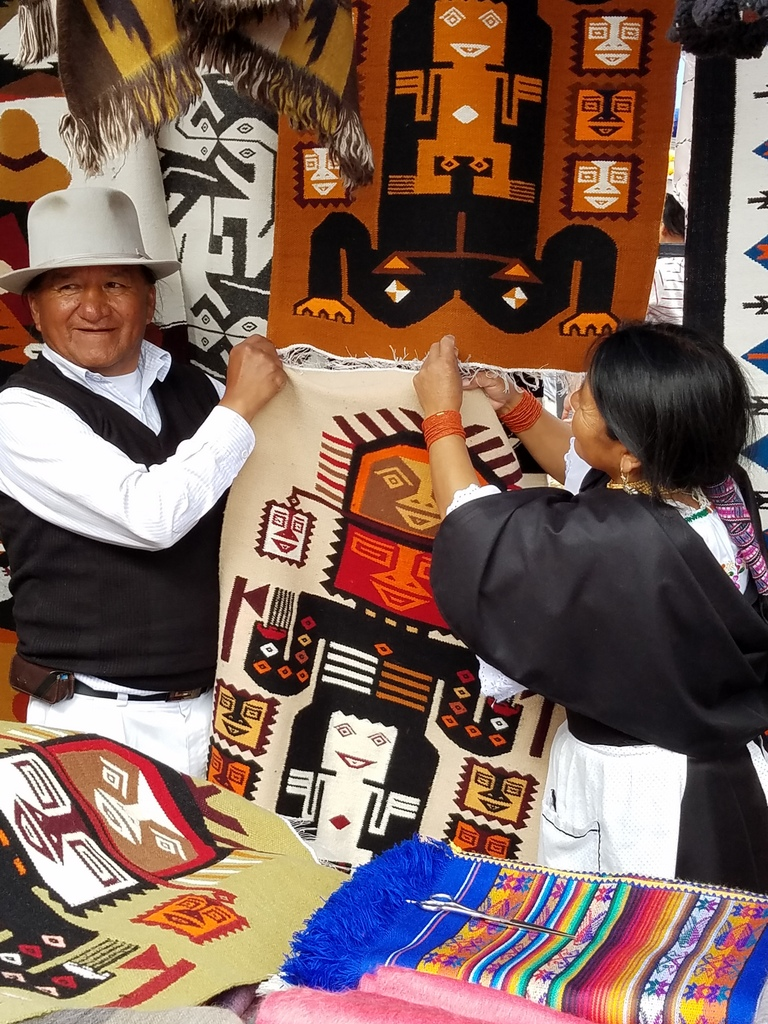 Selling handwoven tapestries in Otavalo market