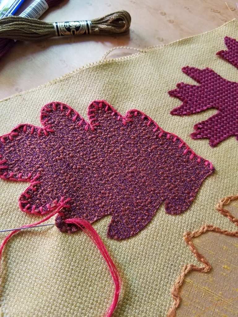 Appliqueing fall leaves onto quilt